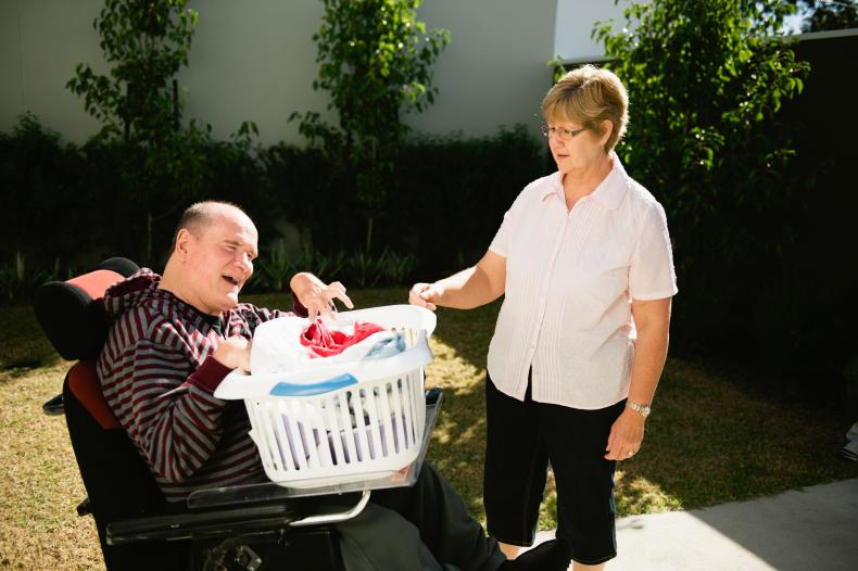 Disability worker helping a man with a disability to hang out the washing