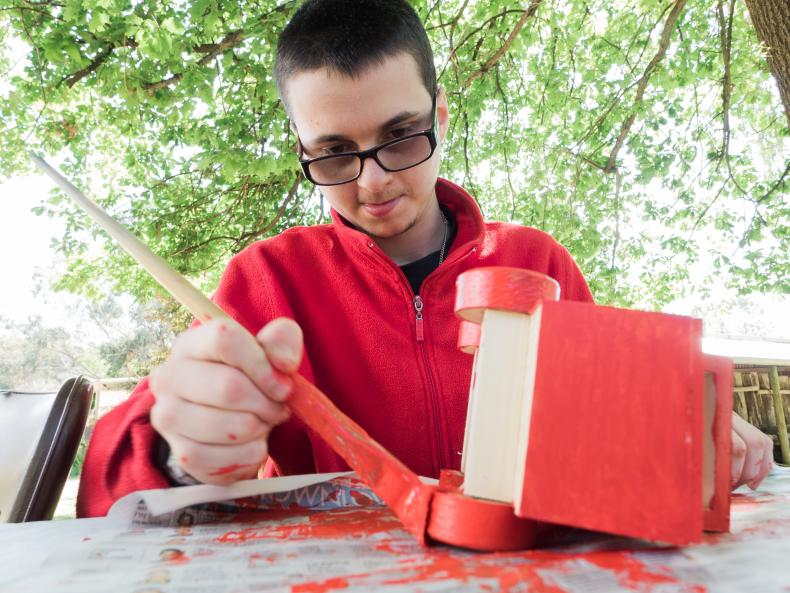 Man with disability painting a red toy truck