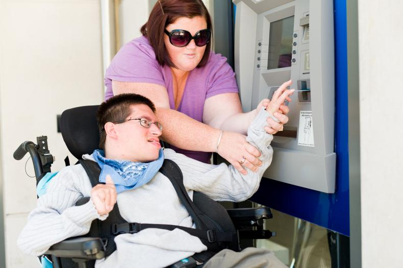 Disability worker assisting a person with disability at an ATM machine